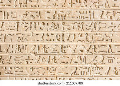 Egyptian hieroglyphs engraved on an ancient stone wall