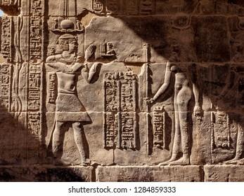 Egyptian hieroglyphs at Philae Temple in Aswan in sunset light