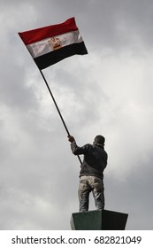 Egyptian holding flag high in Tahrir Square.
