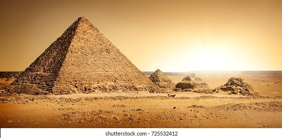 Egyptian pyramids in sand desert and clear sky.