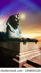 Egyptian sphinx statue on stone pedestal against dramatic sky