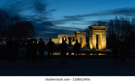 An Egyptian temple reflected in the water in a very blue sunset with gold lights with the shadow of people admiring it.
