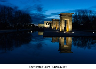 An Egyptian temple reflected in the water in a very blue sunset with gold lights