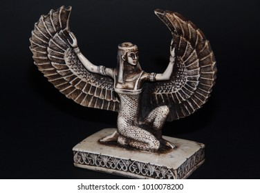 Egyptian winged goddess statue isolated on dark background