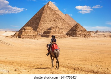 Egyptians on a camel near the complex of Giza Pyramids, Egypt
