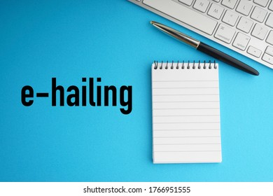 E-HAILING text with fountain pen, keyboard and notepad on blue background. Transportation and Business Concept