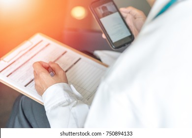 E-Health Doctor. Professional medical physician hand holding smartphone connecting with patient and patient chart information for consulting in clinic hospital. Medical/ healthcare/ technology concept