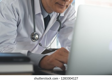 Ehealth, medical online, telemedicine, Electronic medical record system concept. Friendly asian doctor working on laptop computer in medical workspace office, close up.
