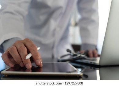 Ehealth, medical online, telemedicine, Electronic medical record system concept. Male doctor with stethoscope reviewing medical document via digital tablet and working on laptop computer in office