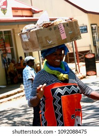 Ehlanzeni, South Africa, 10.31.2016. A black woman wearing national costume sales different tipe of nuts.