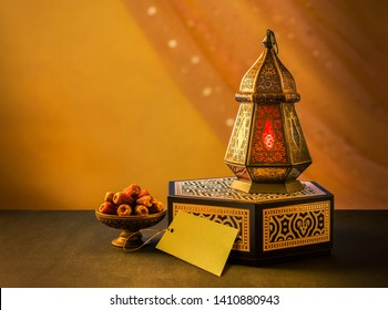 Eid celebration photo with traditional Egyptian lantern, a bowl of dates and a gift box with a blank tag for message. Image for Islamic Season's Greetings.