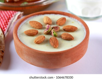 Eid food, Indian or pakistani kheer with golden foil wrapped chocolate balls, Traditional sweet dessert. Iftar meal, christmas celebration.