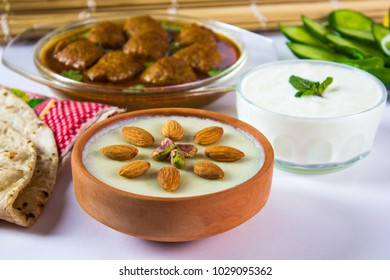 Eid food, Kheer with almond and pistachio toping in soil bowl, Kofta curry with bread, yogurt and vegetable salad.
