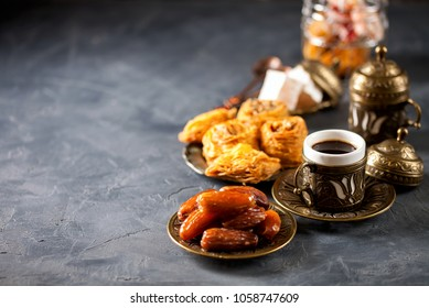 Eid mubarak with arabic coffee pot and dates. Dried dates and coffee on a dark background. Ramadan, Eid concept
