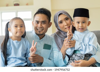 Eid Mubarak celebration moment, Malay family wearing traditional cloth looking at the camera