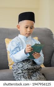 Eid Mubarak celebration moment , Young Malay boy holding Eid cash money envelop