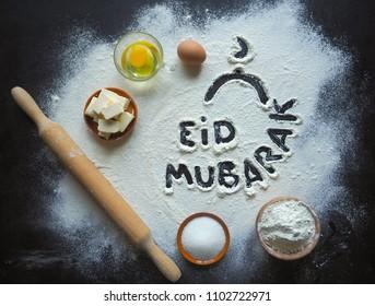 "Eid Mubarak - Islamic holiday welcome phrase "" happy holiday"", greeting reserved. Arabic cuisine background."