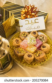 'Eid Mubarak' message in arabic script on a tag along with gift packs and assorted sweet