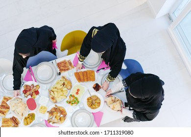 Eid Mubarak Muslim family having Iftar dinner  young muslim girls serving food on the table during Ramadan feasting month at home. The Islamic Halal Eating and Drinking Islamic family top view