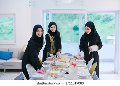 Eid Mubarak Muslim family having Iftar dinner  young muslim girls serving food on the table during Ramadan feasting month at home. The Islamic Halal Eating and Drinking Islamic family