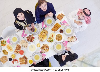 Eid Mubarak Muslim family having Iftar dinner  Eating traditional food during Ramadan feasting month at home. The Islamic Halal Eating and Drinking Islamic family