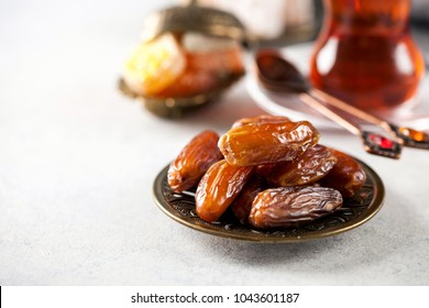 Eid mubarak with  tea and dates. Dried dates and red tea in the Arab glasses on a dark background. Ramadan, Eid concept