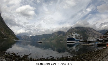 EIDFJORD, NORWAY - 25 JULY 2018: A cruise ship docks with mountains in background