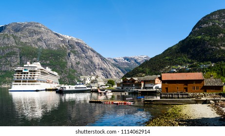 Eidfjord, Norway - May 21, 2018: Travel documentary of everyday life and place. Luxury cruise ship Viking Sun and the smaller ferry Teisten moored in Eidfjord on a sunny day.