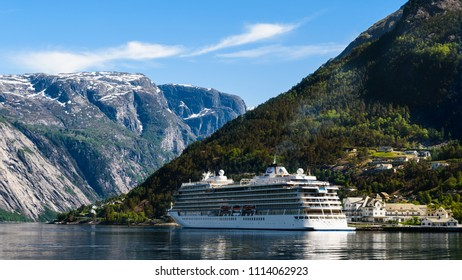 Eidfjord, Norway - May 21, 2018: Travel documentary of everyday life and place. The cruise ship Viking Sun visiting the village on a sunny and calm day. Mountain peaks in the background.
