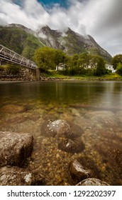 Eidfjord river flowing through the town, mountains covered in the clouds in the background, Eidfjord, Norway