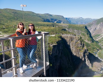 Eidfjord, Waterfall Voringfossen / Norway - June 20 2018: Two happy young women travel and make selfie on smartphone on mountains background