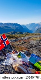 Eidfjord/Norway 5 24 2018: An outdoor picnic items leaning on the rocks: chips, bread rolls and sausage. Norwegian flag waving above. The view on Eidfjord. In the back tall glacier visible