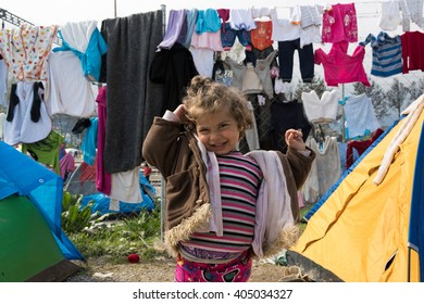 EIDOMENI, GREECE - MARCH 17, 2015: A little girl smiles outside her tent in the refugees camp. For several weeks, more than 10.000 refugees and immigrants wait here for the borders to open.