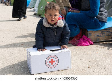 EIDOMENI, GREECE - MARCH 17, 2015: A boy tries to carry a box with supplies given from the Red Cross. For several weeks, more than 10.000 refugees and immigrants wait here for the borders to open.