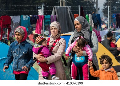 EIDOMENI, GREECE - MARCH 17, 2015: Two women walk with their children in the refugee camp of Eidomeni. For several weeks, more than 10.000 refugees and immigrants wait here for the borders to open.