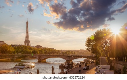 Eiffel Tower against colorful sunset with boat on Seine in Paris, France