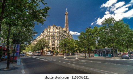 Eiffel Tower behind historic buildings in Paris timelapse hyperlapse, France. Blue cloudy sky at summer day with green trees and traffic on the street