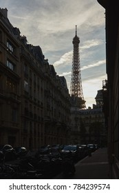 Eiffel tower between buildings in Paris in evening time .