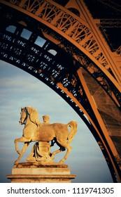 Eiffel Tower closeup and sculpture in Paris, France.