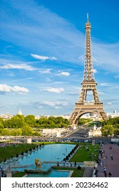 Eiffel Tower, with cloudy blue sky and sunny trees around.