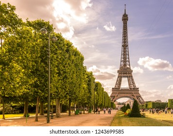 The Eiffel tower in daylight blue sky with some cloud. Champ de Mars park and people in foreground. 7th June 2017, Paris, France.