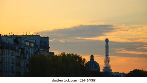 Eiffel tower, dome of Academy of Fine Arts and typical Parisian buildings with attic at sunset. Paris, France. Aged photo. Black and white.