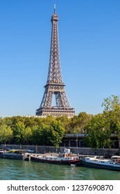 Eiffel Tower during midday. Very sunny day with no clouds in the city. A few boats on the river Seine. Paris, France