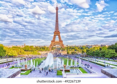 Eiffel Tower and fountain at Jardins du Trocadero against the backdrop of fluffy cloudy sky, Paris, France.