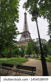 The Eiffel Tower is framed between Spring trees on the Champ de Mars park in Paris, France. A sidewalk leads toward the historic monument. Two empty park benches and a streetlight fill the foreground.