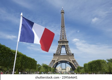 Eiffel Tower with French flag flying in bright summer sky