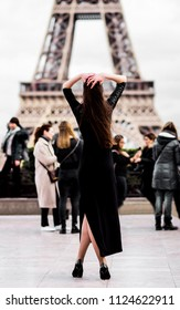 Eiffel Tower. the girl is looking into the distance in a black long dress. concept of fashion style in Paris.
