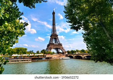Eiffel Tower, iconic Paris landmark across the River Seine with green leaves vibrant blue sky, France