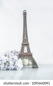 Eiffel tower and lilac flowers on white background, vertical picture