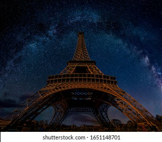 The Eiffel Tower at night under the Milky Way galaxy in Paris, France. Low angle wide perspective view